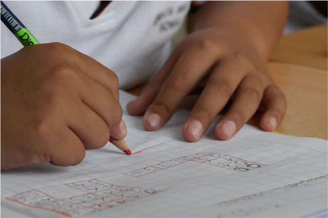 Mãos de estudante escrevendo